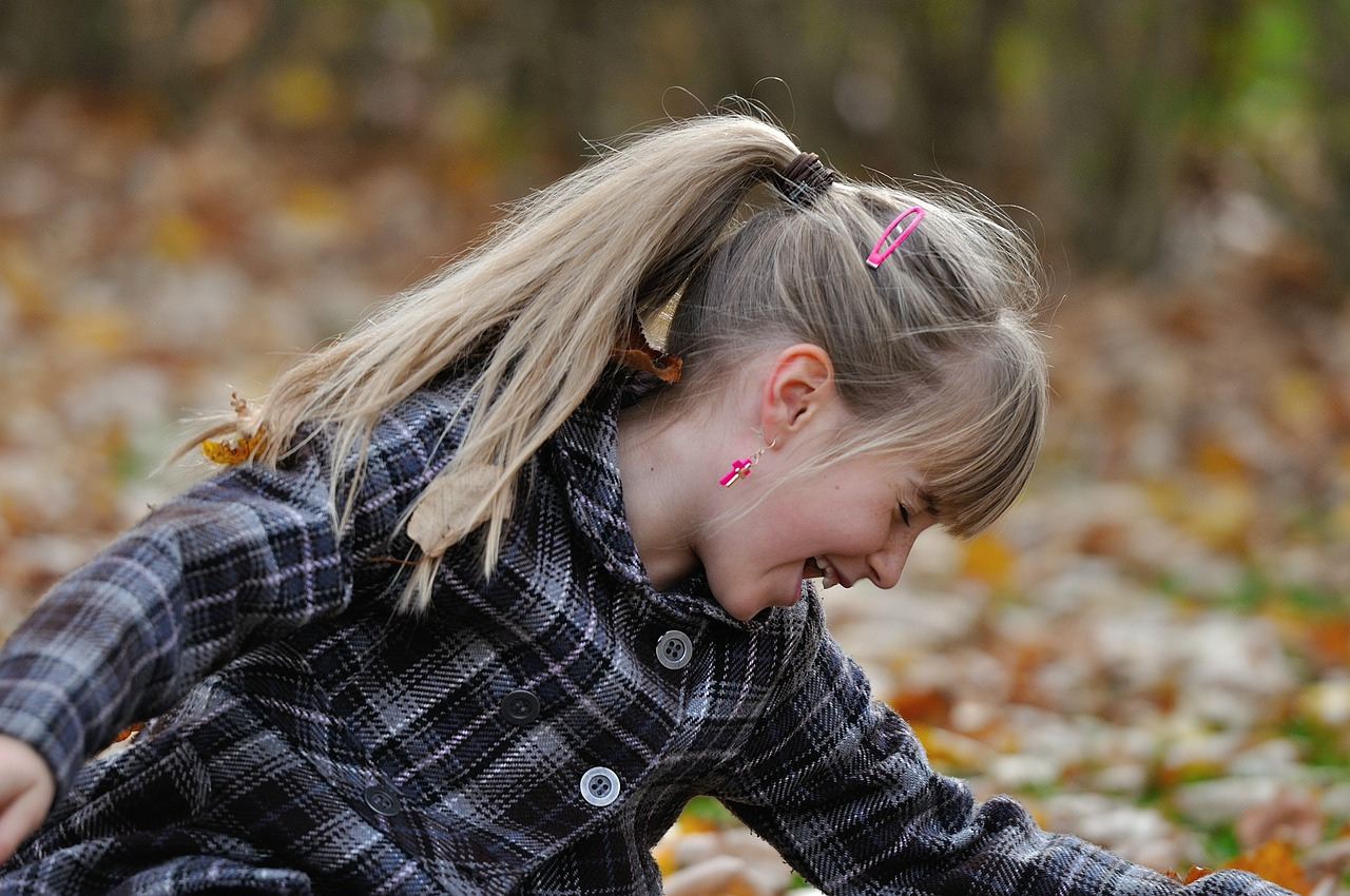 Girl laughing in leaves healed
